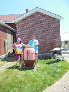 Terri and John with the finished composter painted like a lobster buoy, complete with Seguin's GPS position.