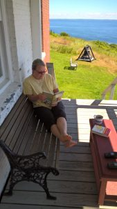 "Patty reading ""Buscano a Alaska"" on the front porch."